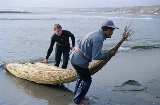 Men dragging reed boat from ocean